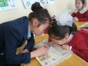 Erdenetuul tutoring a girl in the primary school.